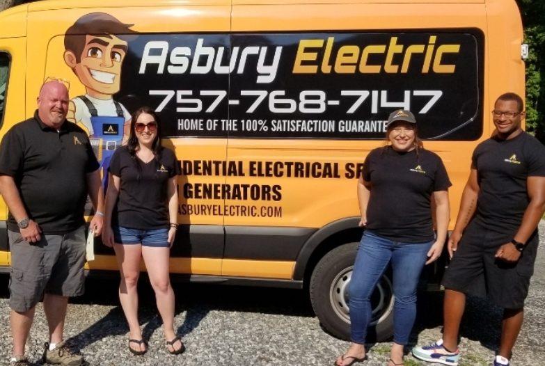 Employees standing in front of Asbury Electric van